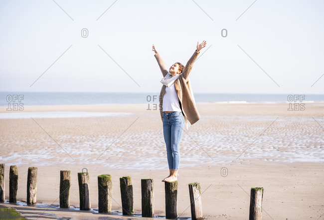 Happy young woman standing on wooden post with arms raised at beach against clear sky during sunny day
