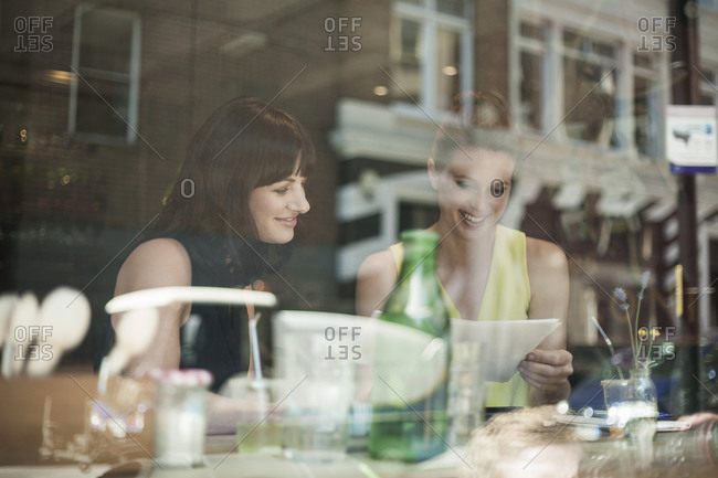 Smiling businesswomen discussing over document during meeting in coffee shop seen through window glass