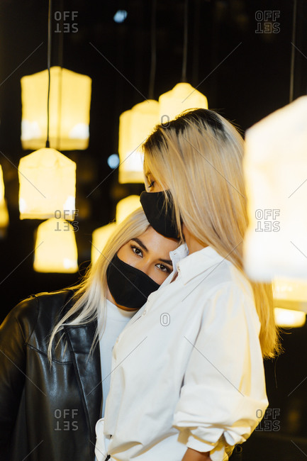 Young woman wearing protective face mask keeping head on friend's shoulder while standing against lamp