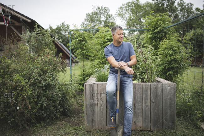 Smiling handsome man holding spade looking away while leaning on wooden raised bed at vegetable garden