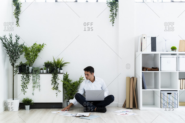 Young businessman analyzing documents while sitting with laptop on floor against white wall in office
