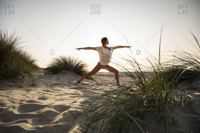 Young woman practicing warrior 2 position yoga amidst plants at beach against clear sky during sunset