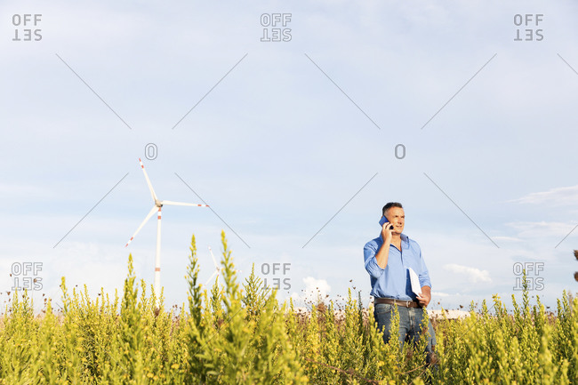 Male engineer talking through mobile phone and document while standing against wind turbines on field