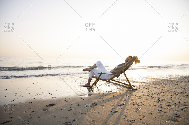 Smiling young woman relaxing while sitting on folding chair at beach against clear sky during sunset
