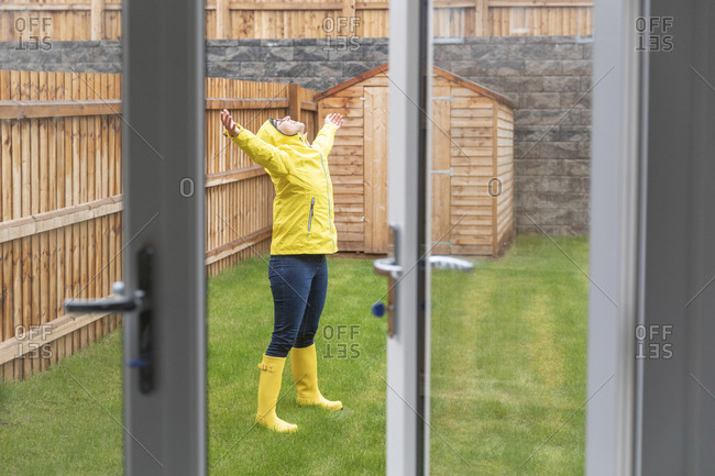 Mid adult woman enjoying rain with arms outstretched while standing in back yard during rainy season