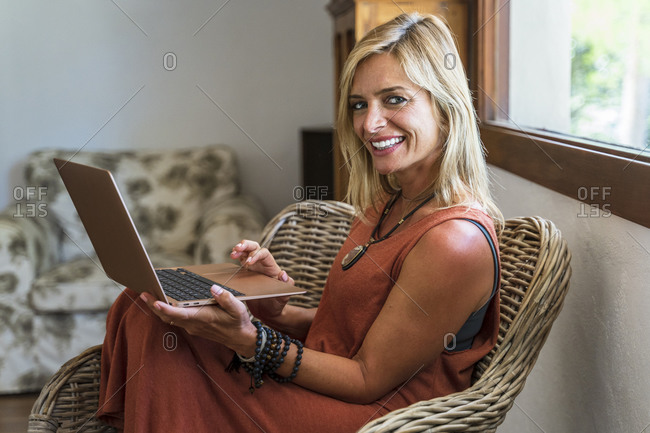 Smiling beautiful blond mature woman holding laptop while sitting on wicker chair at health retreat