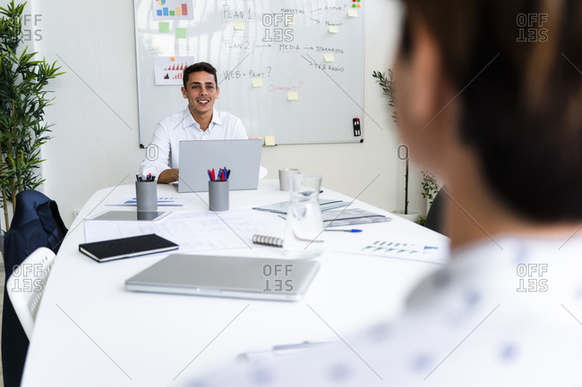 Smiling young male professional discussing with female colleague during meeting in creative office