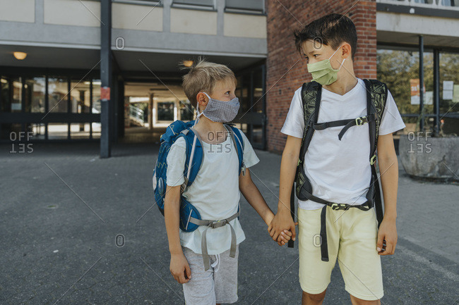 Brothers wearing protective face mask holding hands standing on street in front of school building