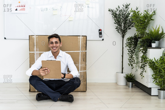 Happy handsome young professional sitting with clipboard on floor against cardboard box in office