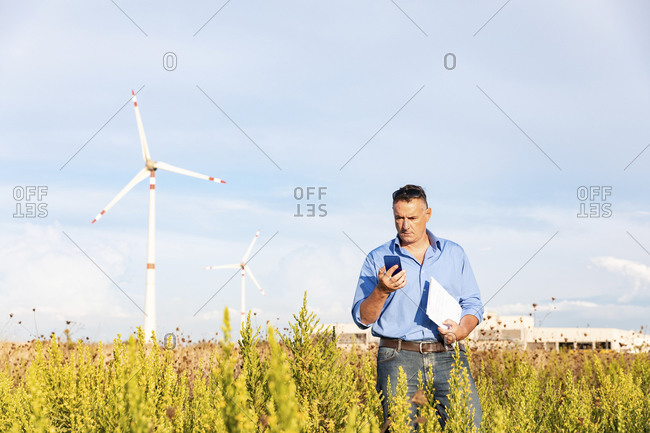Mature businessman holding smart phone and document while standing against wind turbines on field
