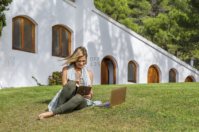 Mature blond woman sitting with diary and laptop on grass against health retreat during sunny day