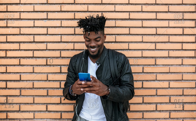 Smiling mid adult man wearing leather jacket using mobile phone while standing against brick wall