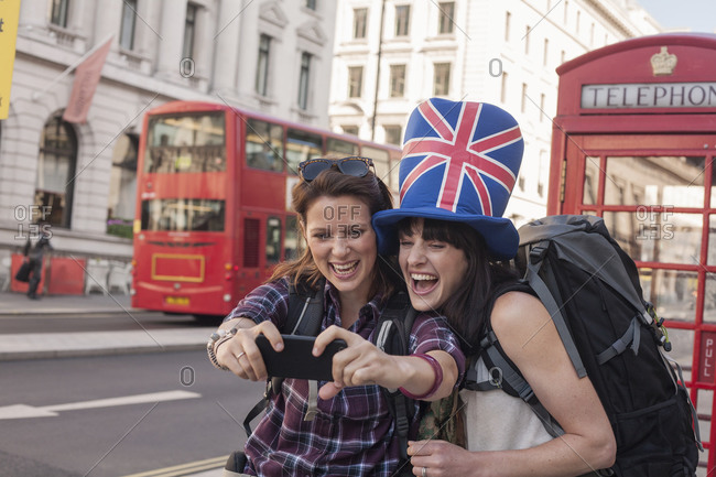 Happy woman taking selfie with friend wearing British flag hat against red telephone box in city