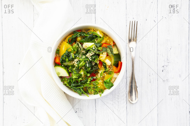Bowl of warm veganquinoasalad with spinach- bell pepper- cucumbers- tomatoes- parsley and mint