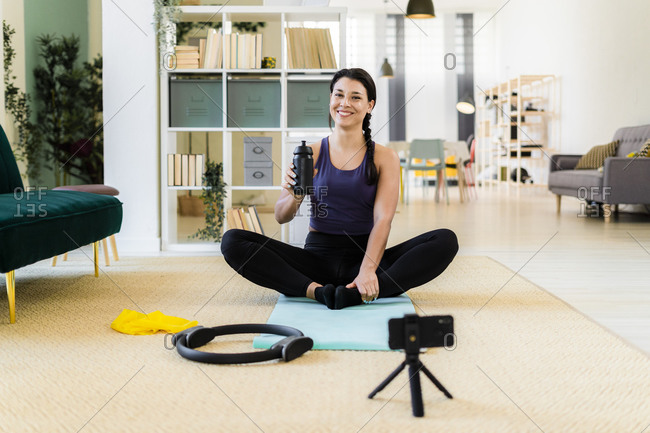 Young woman smiling with bottle video recording on camera while sitting in cobbler pose at home