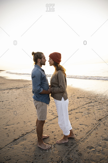 Romantic young couple looking at each other while holding hands standing on shore during sunset