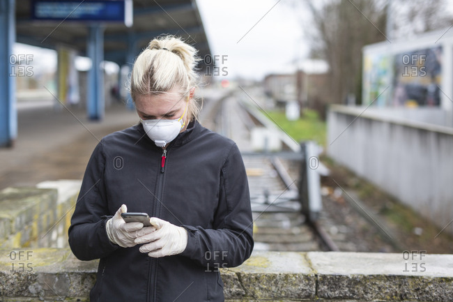 Teenage girl wearing protective mask and gloves using cell phone while waiting at train station