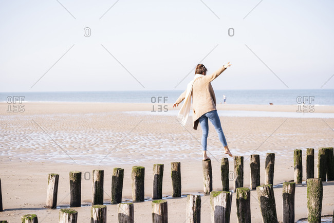 Young woman enjoying walking on wooden posts with arms outstretched at beach during sunny day