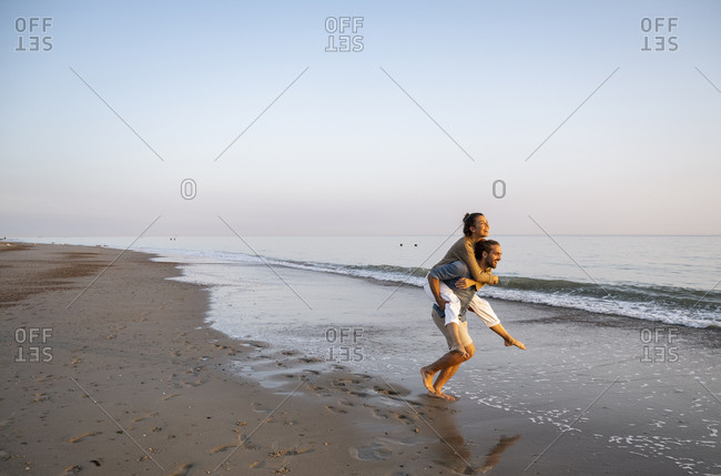 Cheerful man giving piggyback to girlfriend on shore at beach against clear sky during sunset