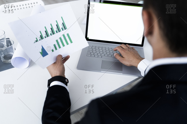 Young businessman analyzing growth graph through laptop while planning at creative workplace