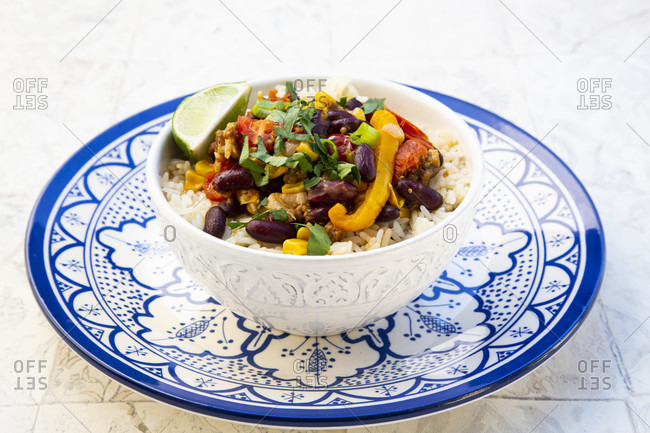 Bowl of Mexican rice with tomatoes- bell pepper- tofu- kidney beans- corn- scallion and lime