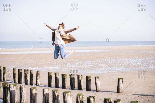 Happy young woman with arms outstretched jumping from wooden posts at beach during sunny day
