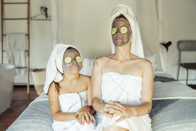Mother and daughter in towel with facial mask and slice of cucumber on eyes sitting at home