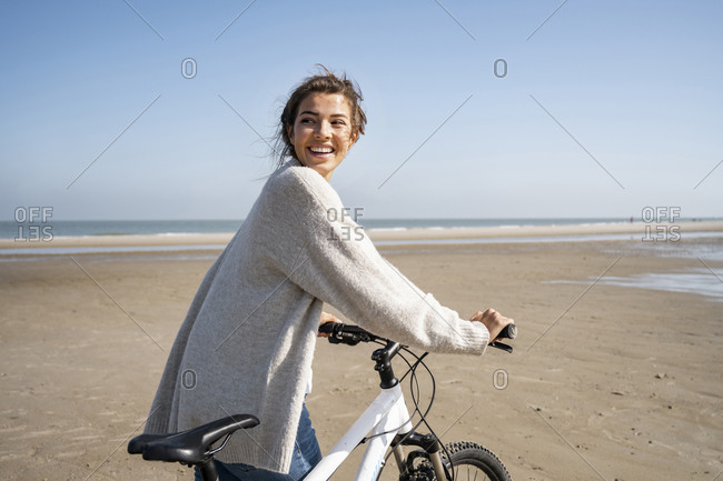 Cheerful young woman walking with bicycle while looking over shoulder at beach on sunny day