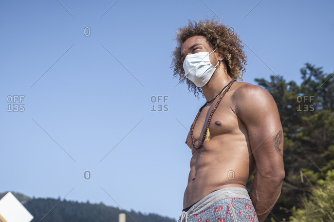 Shirtless young man wearing face mask while standing against clear blue sky during COVID-19