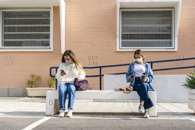 Female teenage friends social distancing while using smart phone sitting on concrete bench