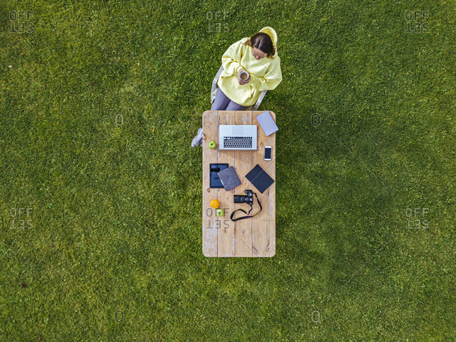 Aerial view of woman sitting at coffee table set on green lawn with mug of coffee in hands