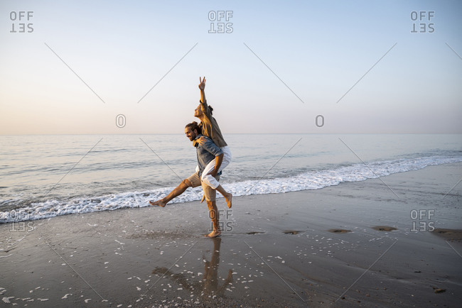 Young man giving piggyback to girlfriend on shore at beach against clear sky during sunset
