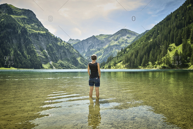 Mature woman standing knee deep in Vilsalpsee while looking at mountain range on sunny day