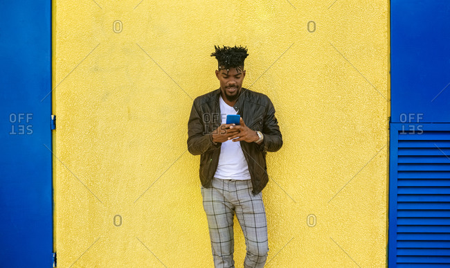 Mid adult man wearing leather jacket using mobile phone while standing against yellow wall