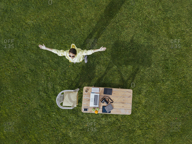 Aerial view of woman standing with raised arms in front of coffee table set on green lawn
