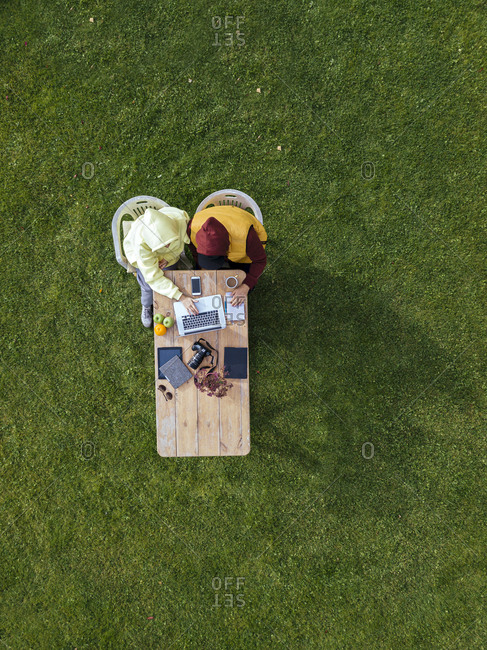 Aerial view of man and woman working together on laptop at coffee table set on green lawn