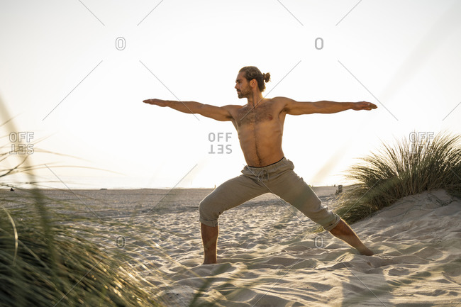 Shirtless man practicing warrior 2 position yoga at beach against clear sky during sunset