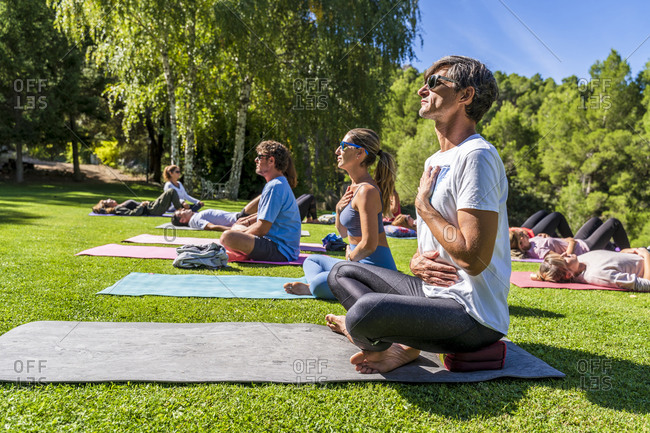 Mature male and female tourists practicing yoga on mat at health retreat during sunny day
