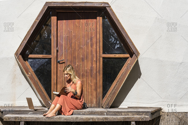 Blond woman reading book while sitting against closed wooden door at retreat on sunny day