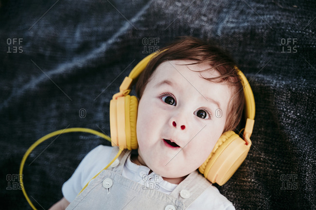 Cute baby boy wearing headphones making facial expression while lying on blanket outdoors