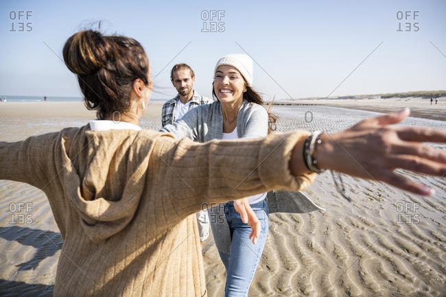 Woman with arms outstretched to hug daughter with men in standing in background at beach