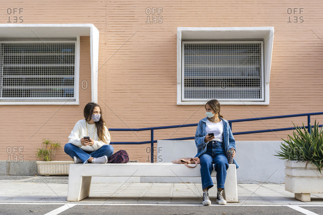 Female friends social distancing wearing protective face mask sitting on concrete bench