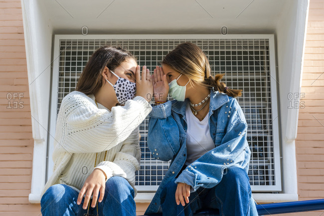 Female friends wearing protective mask sitting face to face on railing during sunny day