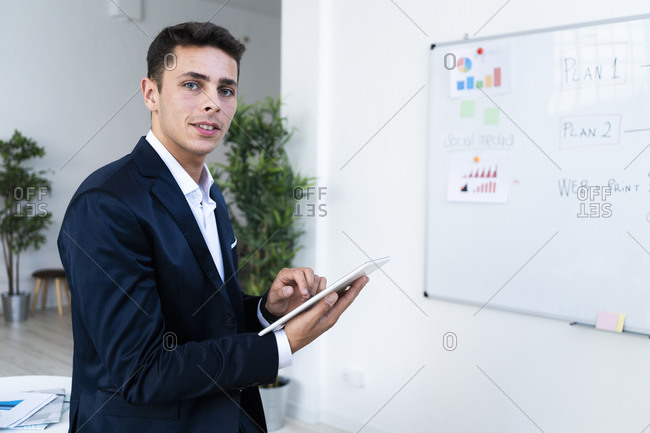 Confident male professional holding digital tablet while standing at creative workplace