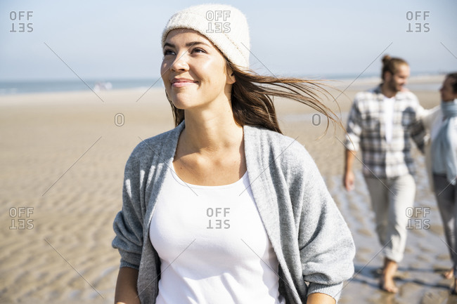 Smiling woman looking up while walking with boyfriend and mother in background at beach