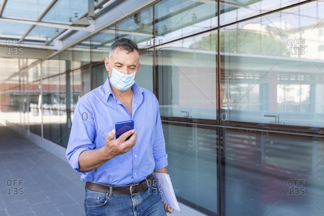 Male entrepreneur using smart phone while walking with document in city during pandemic
