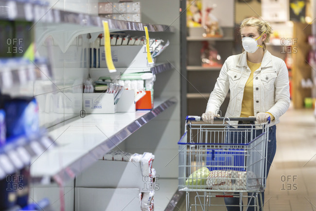 Teenage girl wearing protective mask and gloves looking at empty shelves at supermarket