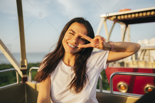 Smiling beautiful woman showing peace sign and winking while enjoying Ferris wheel ride