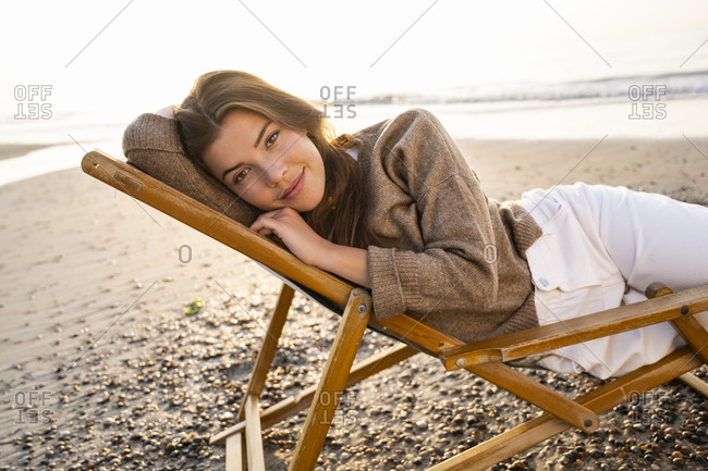 Beautiful young woman relaxing while reclining on folding chair at beach during sunset