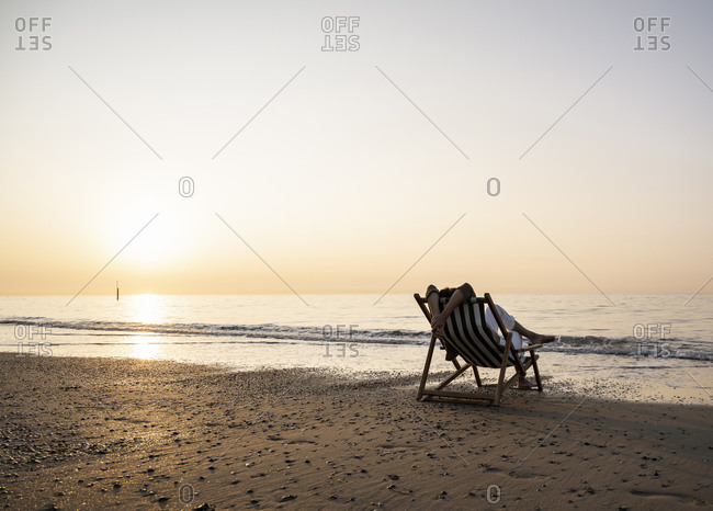 Woman relaxing while sitting on folding chair at beach against clear sky during sunset